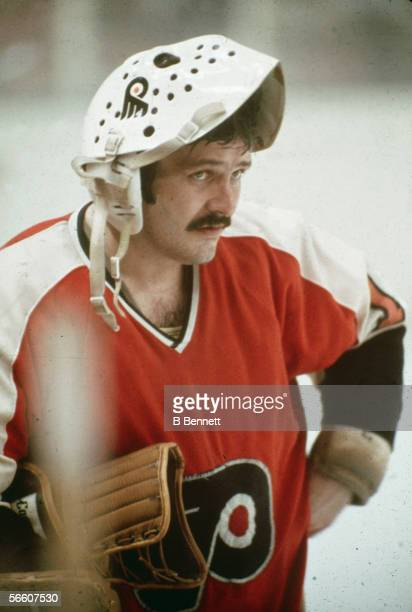 Canadian professional goalie Bernie Parent of the Philadephia Flyers stands on the ice with his face mask flipped up on his head during a 1970s NHL...