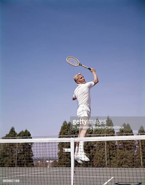 1970s MAN PLAYING TENNIS...