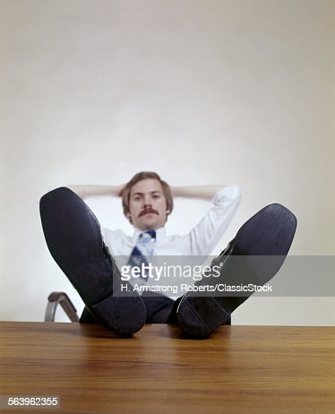 1970s MAN SITTING OFFICE...