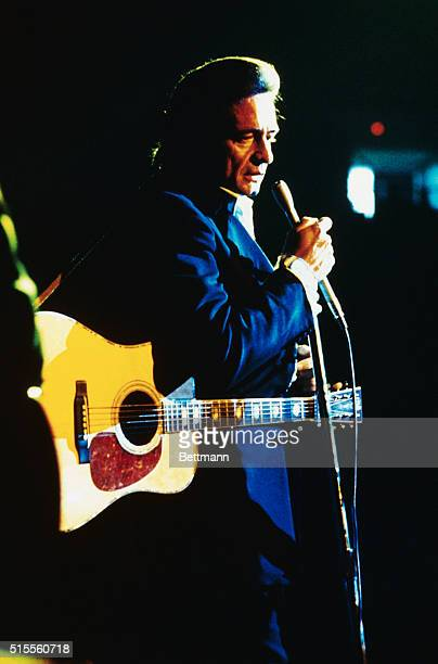 Johnny Cash performing on stage with guitar