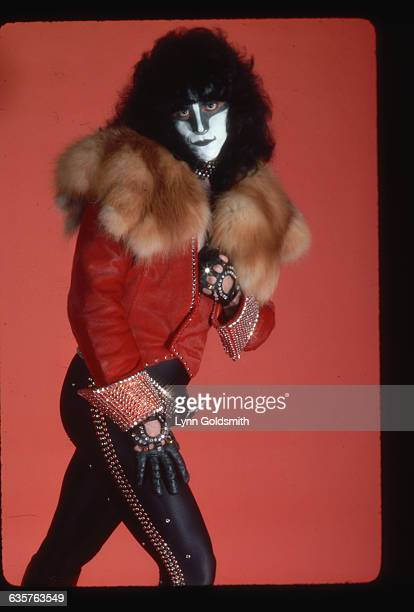 Photo shows Eric Carr drummer with the rock and roll group KISS in a studio portrait in front of a red background He is wearing a furcollared shirt...