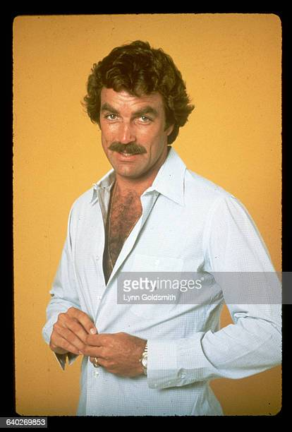 1982Actor Tom Selleck is shown standing in front of a yellow background in a studio portrait buttoning his shirt