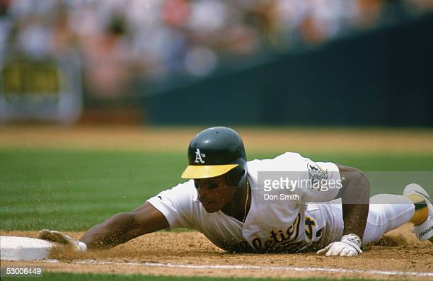 Rickey Henderson of the Oakland Athletics slides head first into the base during a circa 1990s game at OaklandAlameda Coliseum in Oakland California...