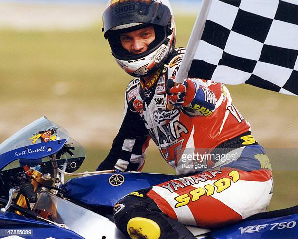 Scott Russell waves the checkered flag during a victory lap after one of his five wins in the Daytona 200 motorcycle race at Daytona International...