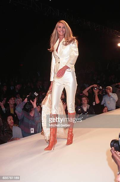 1995New York NY Elle Macpherson models Todd Oldham's fall line She is shown on the runway wearing a white satin jacket and pants with orange kneehigh...