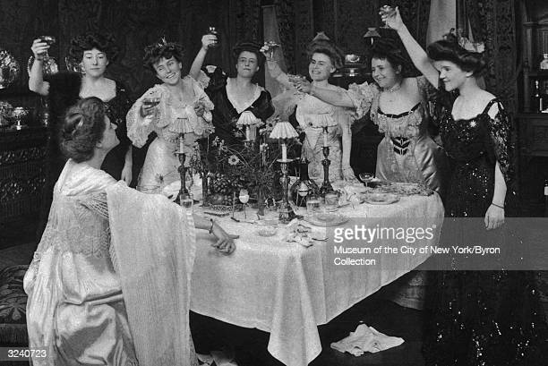A group of women stand around a table and smile while raising their champagne glasses above their heads as they toast a woman sitting at the head of...