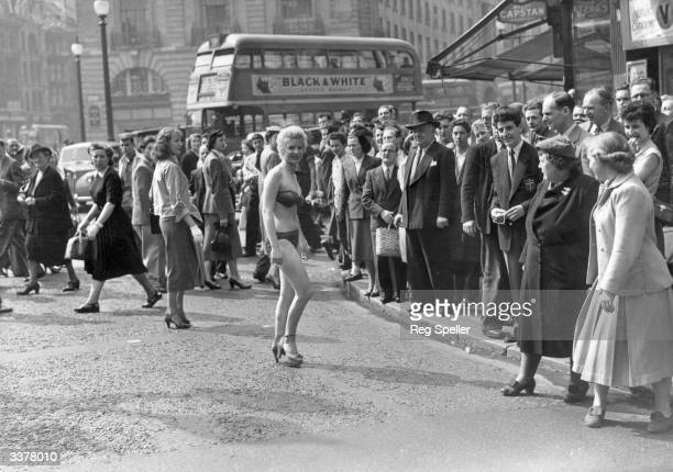 19 year old usherette Margaret Lewis from Carmaethen Wales who lives in Kensington caused a stir in Piccadilly when she decided to beat the heat wave...