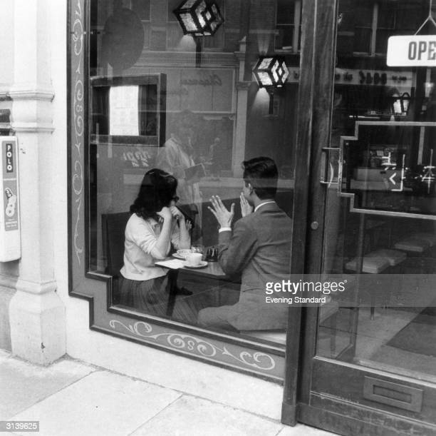 A young couple talking in the window of a coffee bar in London