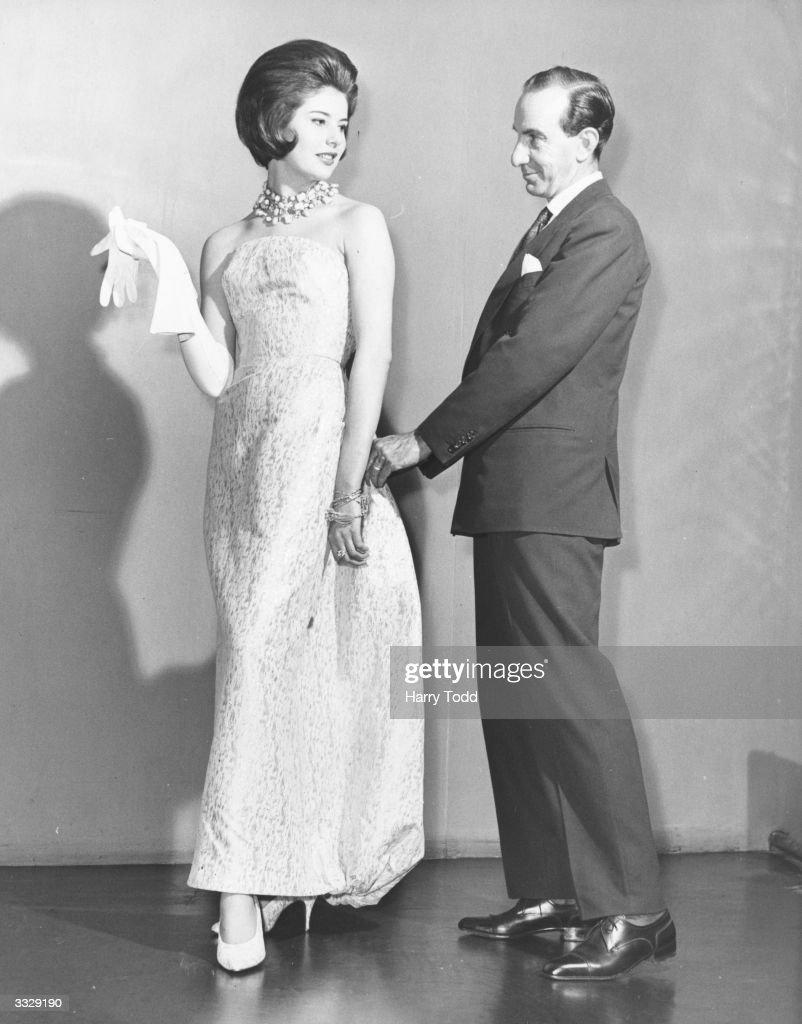Italian designer Emilio Pucci Marchese di Barsento adjusts a white and gold strapless evening dress in 'Emilioform' silk elastic fabric worn by model...
