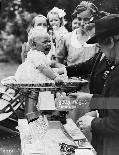 A young competitor at a baby show objects to being weighed