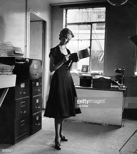A woman wearing a black satin dress by Brenner with baby lace around the sleeves neck and hemline which is not really suitable for the office...