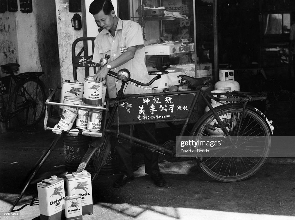 A worker at a service station for Chinese fishing junks in Aberdeen Harbour, Hong Kong, loads a bicycle with cans of petrol and oil.
