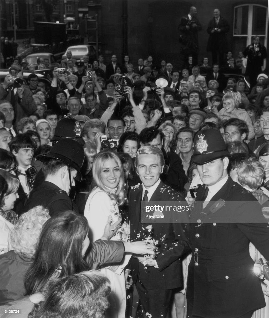 Pop singer and actor Adam Faith (1940 - 2003) with his wife Jackie Irving surrounded by fans and police after their wedding at Caxton Hall registry office in London.