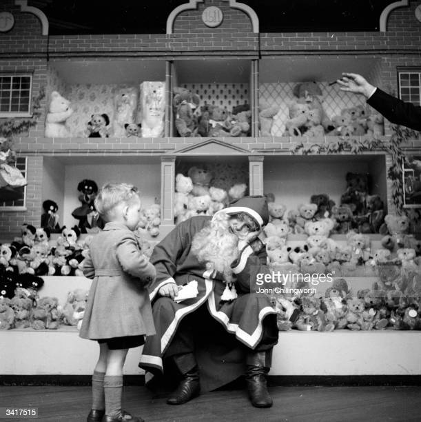 A resolutely tired Denzil Batchelor in costume as Father Christmas wearily answers another child's question at Harrods department store in London...