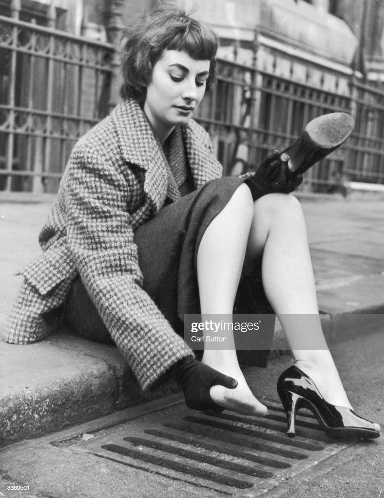 Dancer and model Jeann Marsh demonstrates how the new stiletto heel, which has just arrived in London from Paris, can be hazardous around town. Original Publication: Picture Post - 6833 - The Hazards Of The Stiletto Heel - pub. 1953