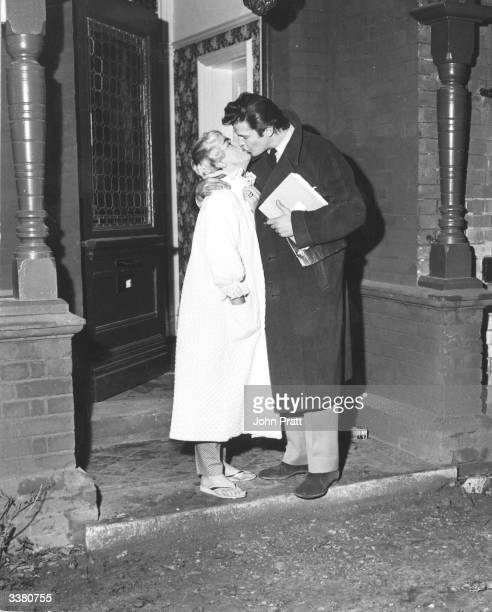 Roger Moore kissing his wife Welsh singer Dorothy Squires outside their home in Bexley Heath London