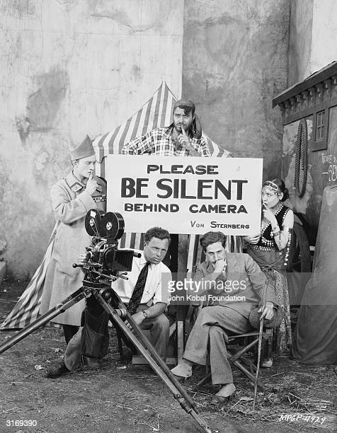 Conrad Nagel and Renee Adoree are positioned on either side of a sign reading 'Please be silent behind camera' on the set of 'The Exquisite Sinner'...