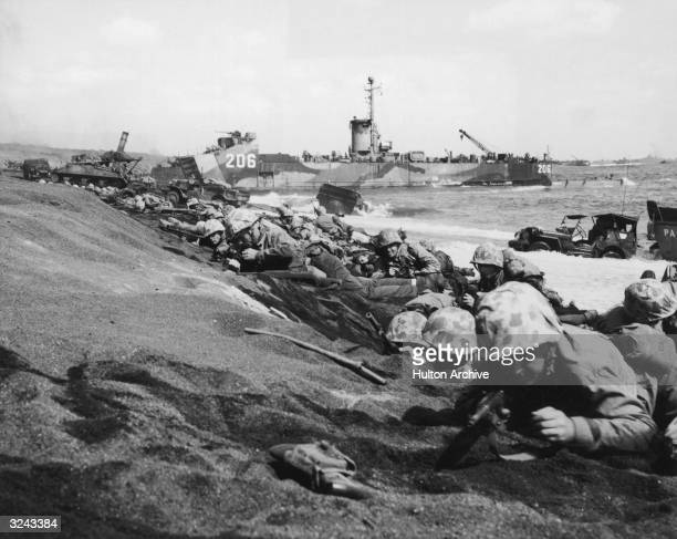 United States Fourth Division Marines take cover from enemy fire on the shores of Iwo Jima during World War II Japan A US battleship and amphibious...