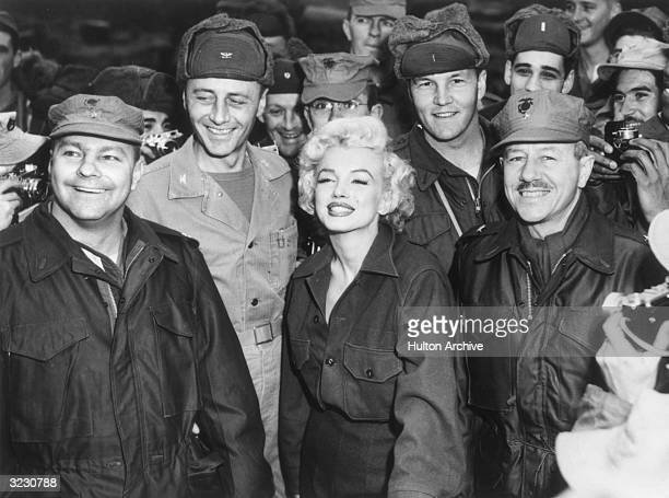 American actor Marilyn Monroe smiles while posing with soldiers while entertaining US troops stationed in Korea Monroe wears a military uniform
