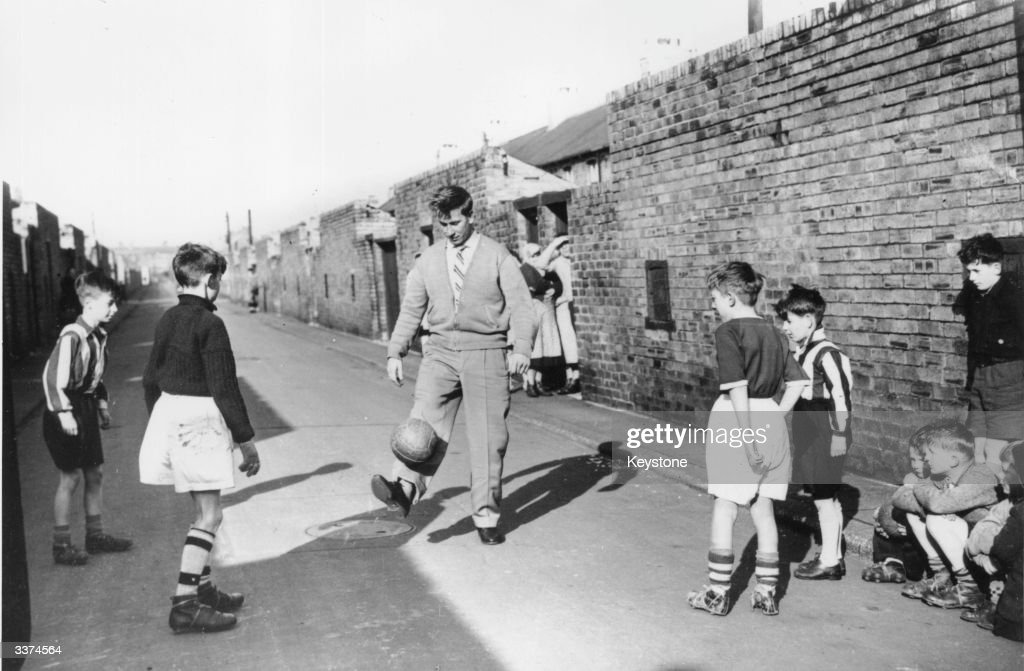 Footballer Bobby Charlton of Manchester United gets back into gentle training with some young fans in the backyard of his home on Beatrice Street...