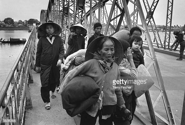 A group of Vietnamese refugees crossing a bridge over the Perfume River during war in Vietnam