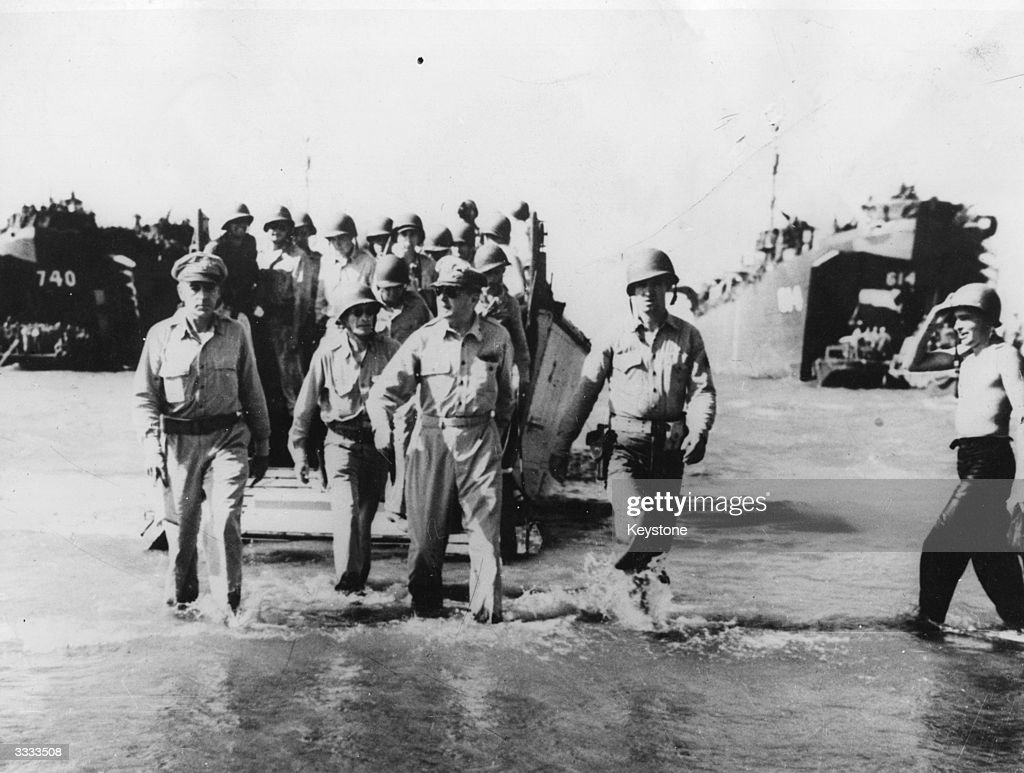 US General Douglas MacArthur (1880 - 1964), goes ashore from a landing craft with a party of the invading force at Luzon.