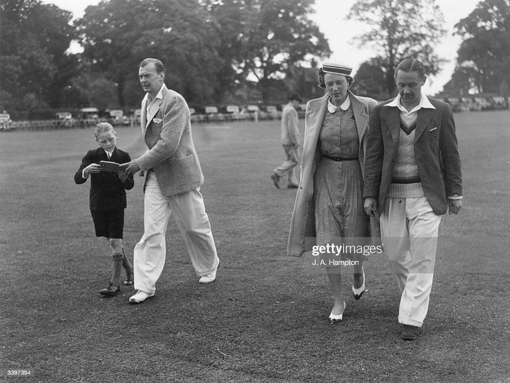 Ian Peebles (1908- 1980) cricket (bowler) player for Middlesex and England (1927 - 1931) returning an autograph book to a boy fan. Mrs A P F Chapman and George 'Gubby'Allen (1902 - 1989) cricket player for Middlesex and England (1930 - 1948), Knighted in 1986.