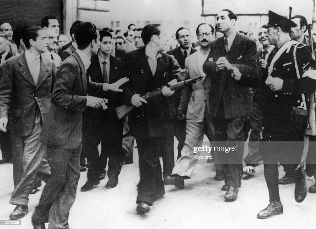 In Rome, an angry crowd of armed anti-Fascist civilians helps a policeman escort an ex-'Big Shot' of the Fascists to the jail where he will be held until tried for crimes committed under the Mussolini regime.
