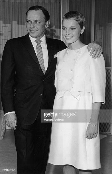 American singer Frank Sinatra stands with his arm around his third wife actor Mia Farrow during their private wedding in Las Vegas Nevada Sinatra...