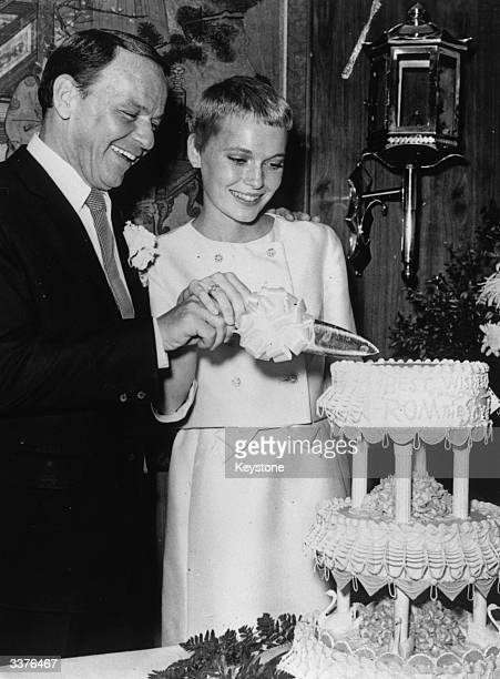 Singer Frank Sinatra and actress Mia Farrow cutting their wedding cake at Las Vegas