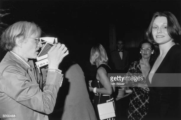 American artist Andy Warhol taking a photograph of British author and actor Tessa Dahl with his Polaroid camera during a Mother's Day party at the...