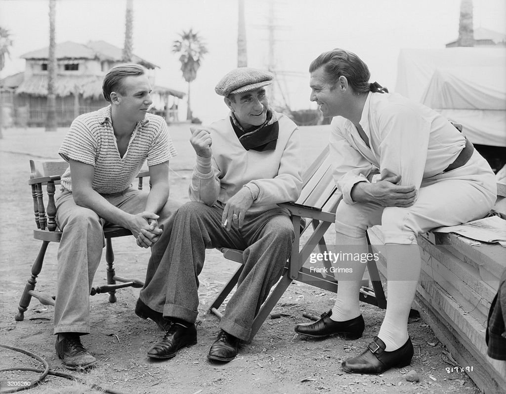 American actor Clark Gable (1901 - 1960) converses with director Frank Lloyd (1886 - 1960) on the set of 'Mutiny on the Bounty'.