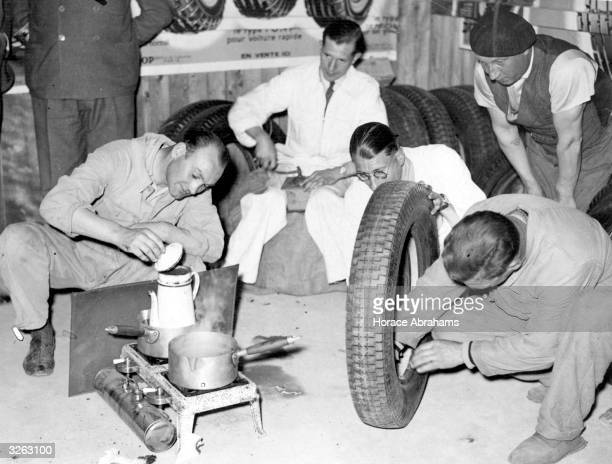 British racing car mechanics cooking supper and repairing tyres in the pits during the Le Mans 24 Hour Race