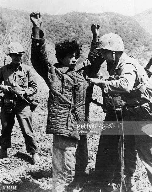 An American Marine searching a captured Chinese Communist in Korea