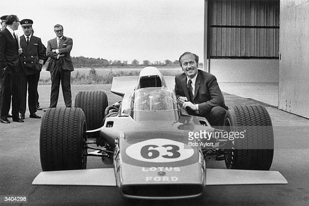 Designer Colin Chapman with the new 1969 Lotus 63 with driver John Miles at the wheel as the car makes its debut at the Lotus factory at Norwich...
