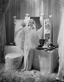 Dressed in a white lurex evening gown Jean Harlow makes a telephone call from her luxurious bedroom in a scene from the fim 'Dinner at Eight'...