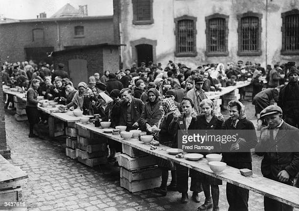 European refugees eating at a dispersal point at the former German political prison at Ansalt