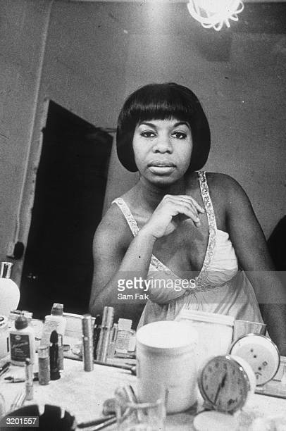 Headshot of American singer and musician Nina Simone seen in her dressing room mirror seated at her makeup table at the Village Vanguard before a...