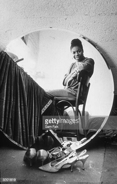 Seated portrait of American singer Nina Simone seen reflected in a round mirror in her dressing room at the Village Gate before a live recording...