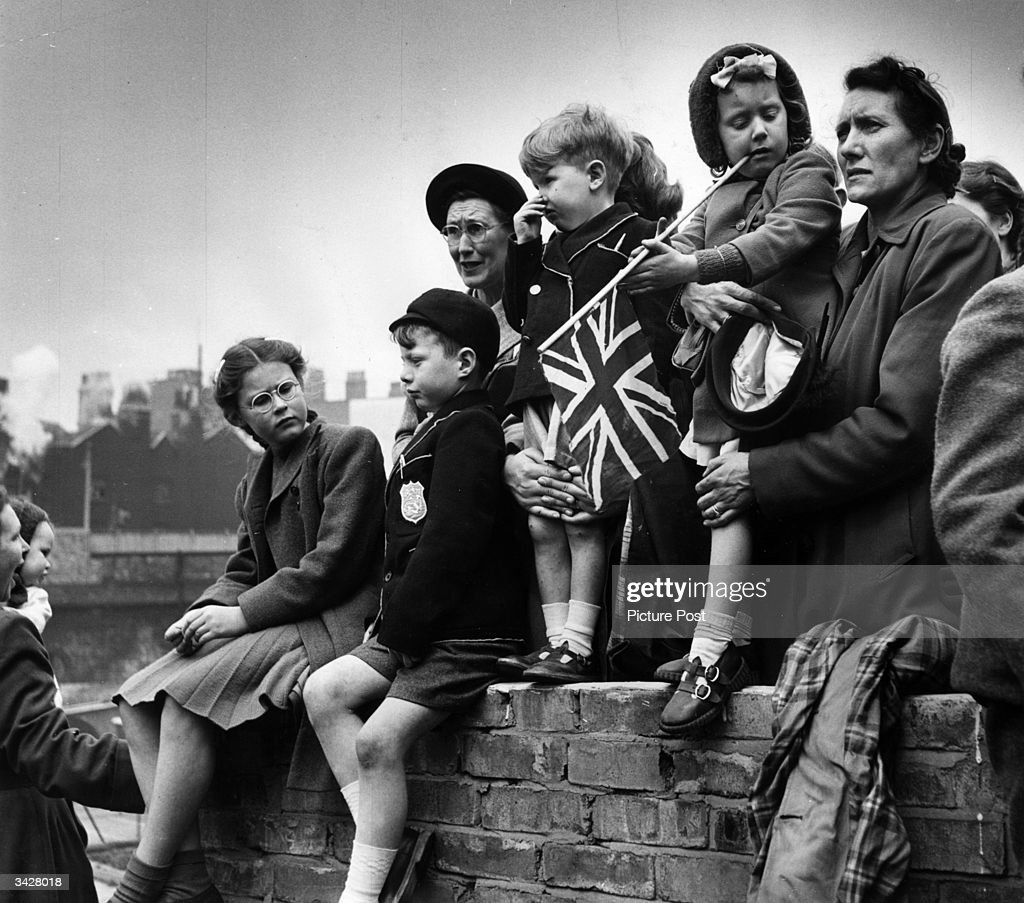 Families watching the Royal procession as King George VI goes to St Paul's to declare the Festival of Britain open. Original Publication: Picture Post - 5306 - The Royal Opening To Britain's Festival - pub. 1951