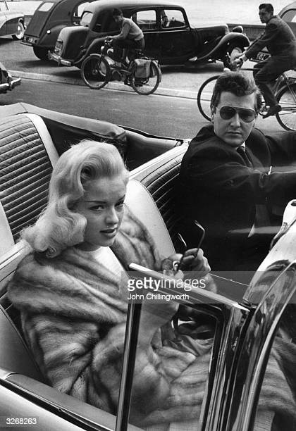 British blonde 'bombshell' actress Diana Dors formerly Diana Fluck with her husband in a light blue cadillac at the Cannes Film Festival to promote...