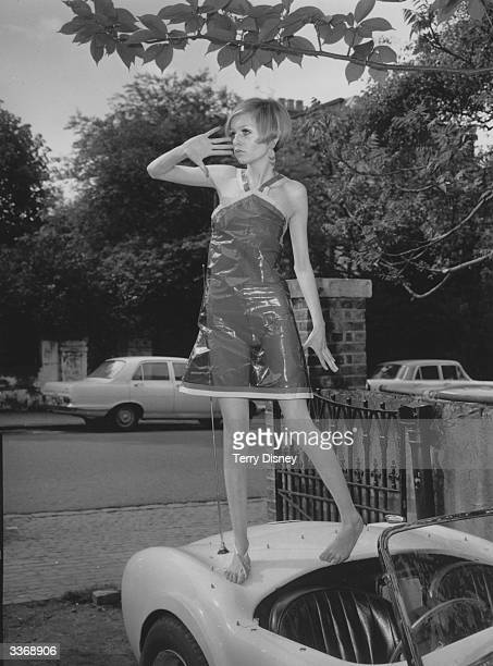 British model Twiggy wearing a transparent plastic halterneck dress standing on the boot of a car