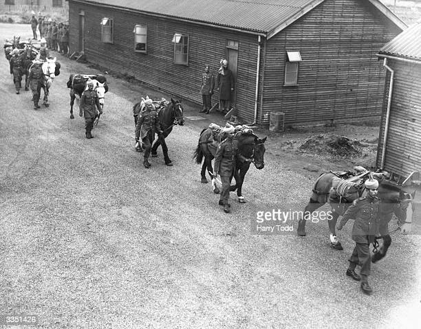 Soldiers of the Royal Indian Army stationed at the RIASC Colchester in Essex leading their horses across the parade ground