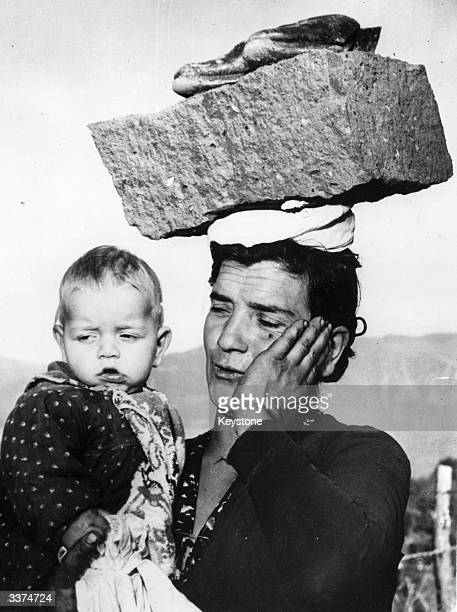 An Italian pilgrim carries her young son with one arm and a large stone and her shoes on her head en route to a site in Visciano to assist a priest...