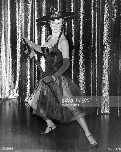 Promotional portrait of American singer and actor Doris Day posing on stage modeling her costume designed by Leah Rhodes for director David Butler's...
