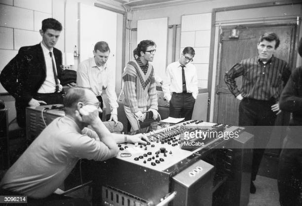 Cliff Richard in a stylish sweater listens as the producer and recording technician makes some adjustments in a recording studio of EMI in London...