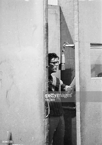 Seen through a half open door pop singer Cliff Richard at the microphone