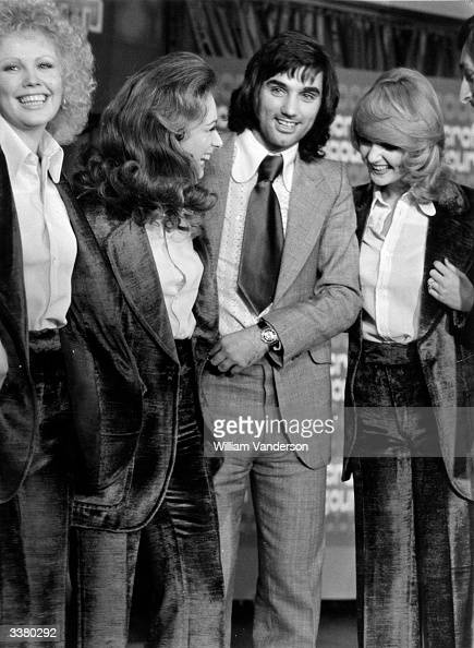 Manchester United footballer George Best with three women wearing matching velvet suits