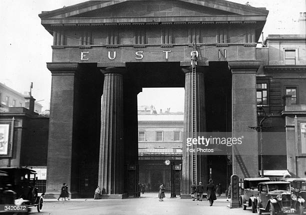 Workmen regilding the lettering on the arch at Euston Station in London It was demolished in 1962