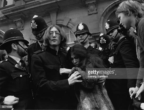 Beatles singer songwriter and guitarist John Lennon and his partner artist Yoko Ono leaving court surrounded by police